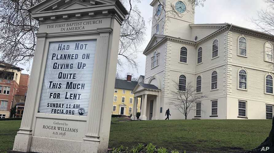In this March 24, 2020, photo, a man walks past the First Baptist Church in America in Providence, R.I. Americans are turning…
