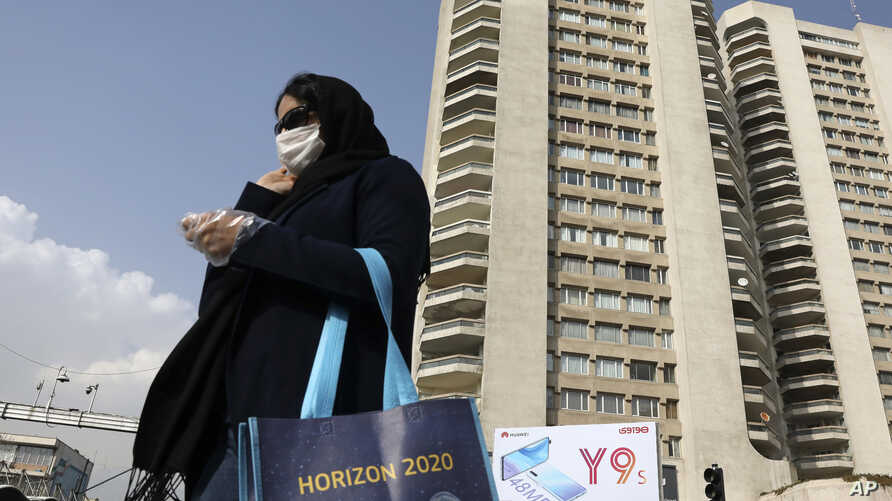 A pedestrian wearing a face mask crosses a street in northern Tehran, Iran, Sunday, March 1, 2020. While the new coronavirus…