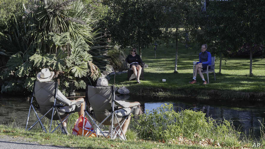 Neighbors chat across a stream as they practice social distancing in a suburb of Christchurch, New Zealand, Sunday, April 5,…
