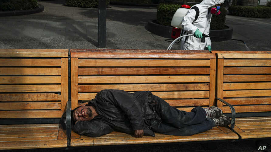 A city worker sprays disinfectant while a man sleeps on a bench in the Plaza de Armas in Santiago, Chile, Wednesday, April 15,…