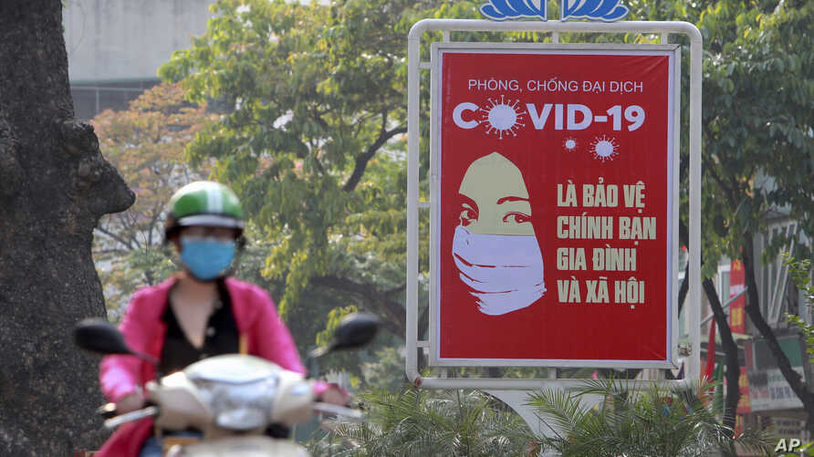 A motorcyclist drives past a poster calling people to take care of their health against the new coronavirus in Hanoi, Vietnam…