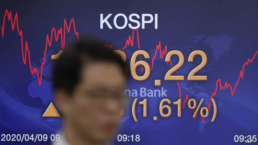 A currency trader walks by the screen showing the Korea Composite Stock Price Index (KOSPI) at the foreign exchange dealing…