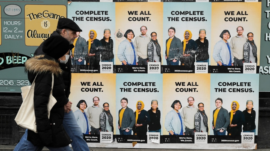 FILE - In this  Wednesday, April 1, 2020 file photo,People walk past posters encouraging participation in the 2020 Census in…
