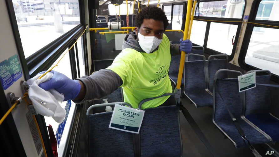 Robert Day works on disinfecting surfaces on a bus in Detroit, Wednesday, April 8, 2020. Detroit buses will have surgical masks…