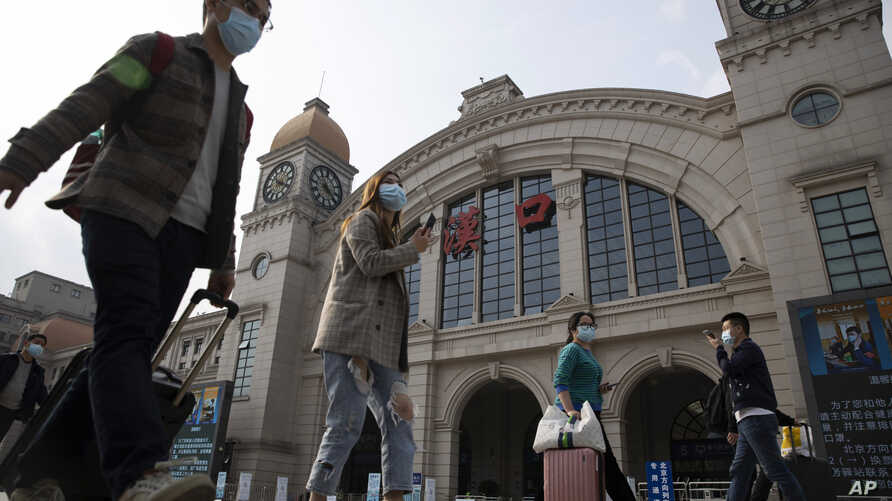 Travelers with their luggage walk past the Hankou railway station on the eve of its resuming outbound traffic in Wuhan in…