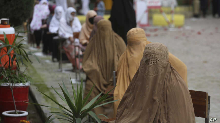 Women wait to receive cash under the governmental Ehsaas Emergency Cash Programme for families in need, during a government…