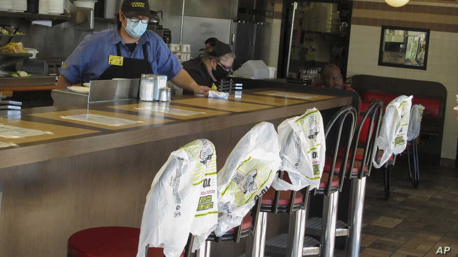 Plastic bags mark off seats to promote social distancing at a Waffle House restaurant in Savannah, Ga., on Monday, April 27,…