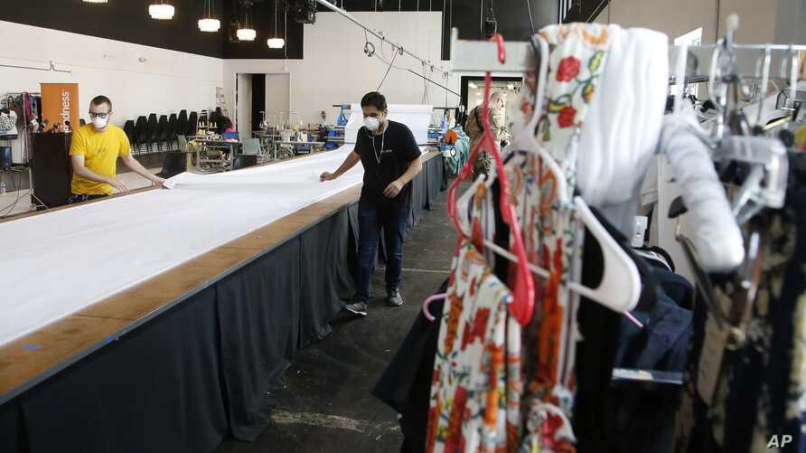 Workers at F.A.B.R.I.C., a non-profit organization providing resources for emerging fashion designers, fold a large roll of…