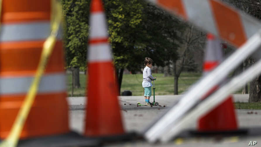 A child rides a scooter past barricades at an entrance to Tower Grove Park Tuesday, March 31, 2020, in St. Louis. The entrance…