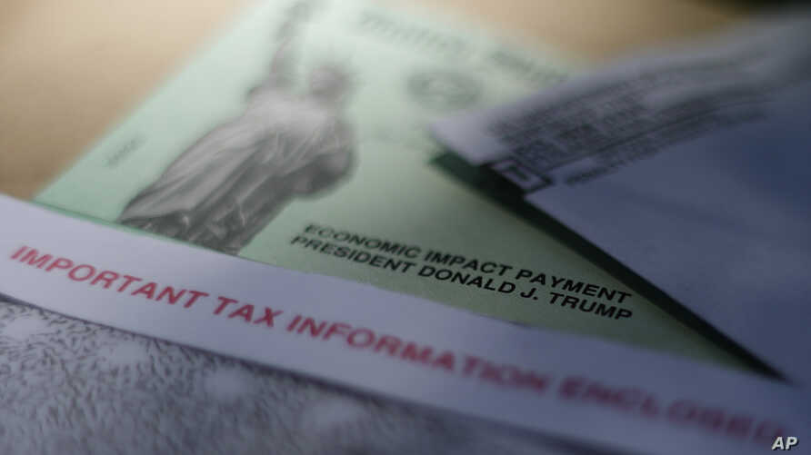 FILE - This April 23, 2020, file photo shows President Donald J. Trump's name printed on a stimulus check issued by the IRS to…