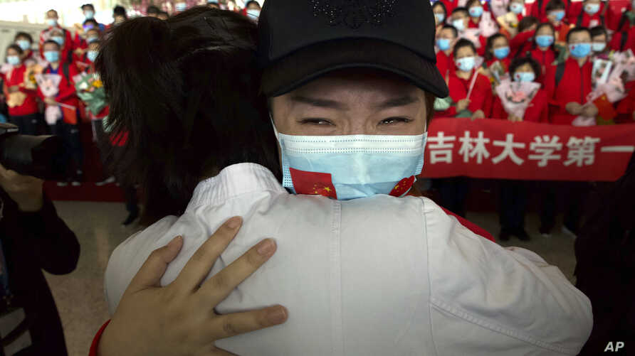 A medical worker from China's Jilin Province reacts as she prepares to return home at Wuhan Tianhe International Airport in…