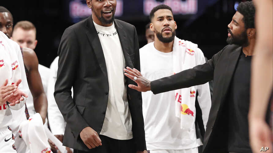 Injured Brooklyn Nets guard Kyrie Irving, right, puts his hand on fellow injured player Kevin Durant who smiles as he stands to…
