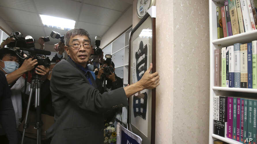 Lam Wing-kee, one of five shareholders and staff at the Causeway Bay Book shop in Hong Kong, hangs his congratulatory gift,…