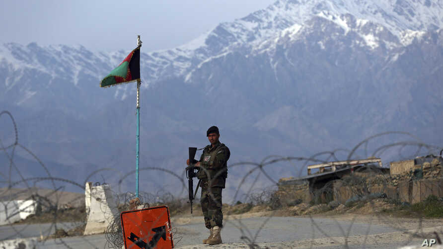 FILE - In this Wednesday, April 8, 2020, file photo, an Afghan National Army soldier stands guard at a checkpoint near the…