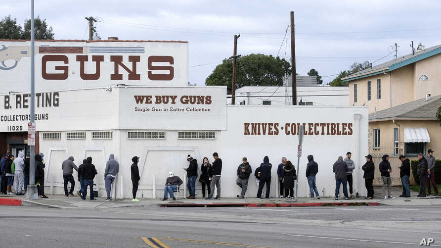 People wait in a line to enter a gun store in Culver City, Calif., Sunday, March 15, 2020. Coronavirus concerns have led to…