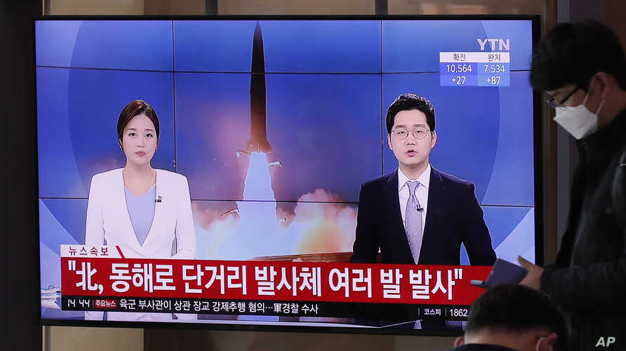 A man wearing a face mask walks past a TV screen airing reports about North Korea's firing of missiles at the Seoul Railway…