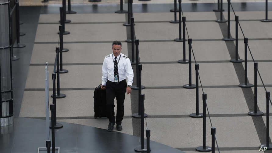 A pilot heads through the empty south security checkpoint as a statewide stay-at-home measure to stem the rapid spread of the…