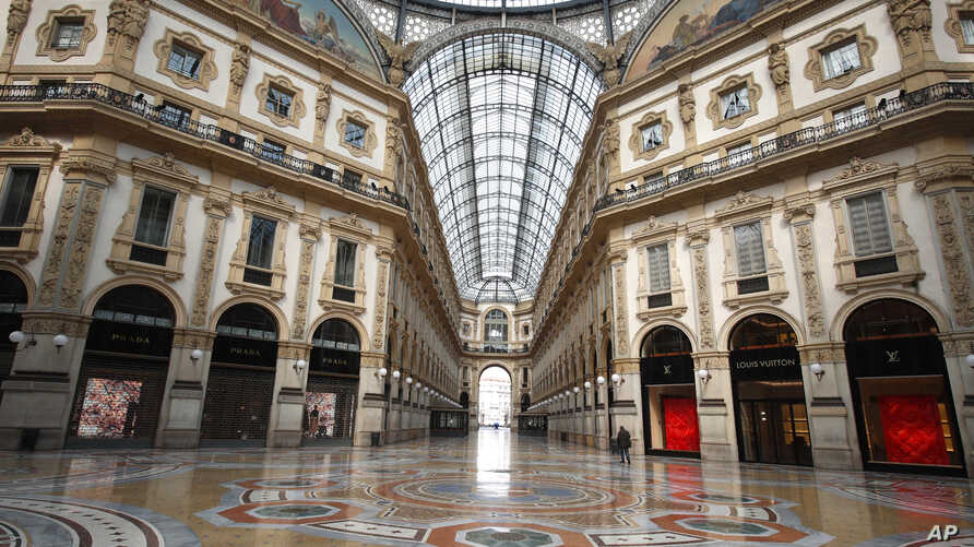 FILE - In this Sunday, March 22, 2020 filer, a man walks in an empty Vittorio Emanuele II gallery shopping arcade, in downtown…