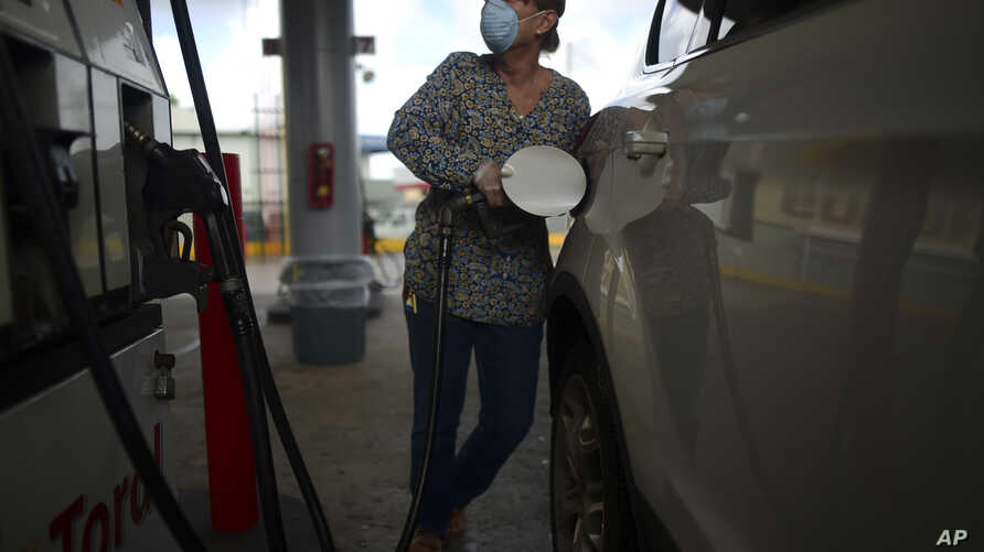 A woman wears a face mask and gloves at the gas station during a government ordered quarantine aimed at curbing the spread of…
