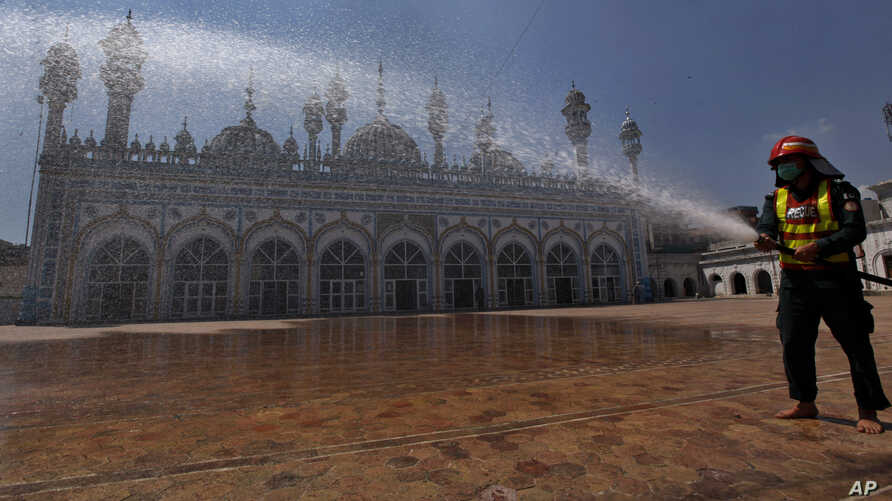 A rescue worker sprays disinfectant in the courtyard of a mosque in an effort to contain the outbreak of the coronavirus ahead…
