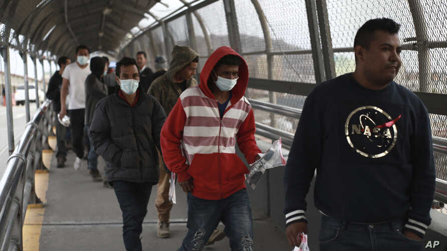 Central American migrants seeking asylum, some wearing protective face masks, return to Mexico via the international bridge at…