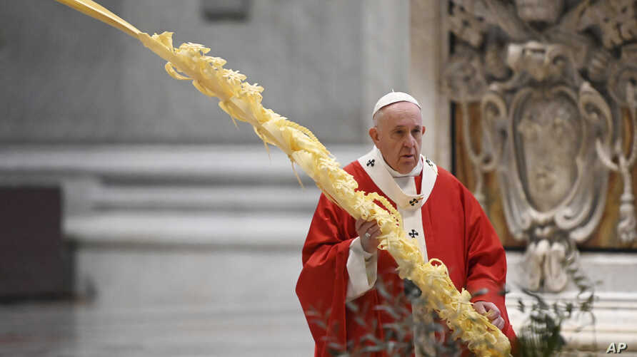 Pope Francis holds a palm branch as he celebrates Palm Sunday Mass behind closed doors in St. Peter's Basilica, at the Vatican,…