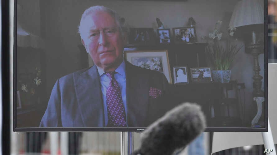 A view of Britain's Prince Charles projected on a screen as he pauses prior to delivering a video message from his residence in…