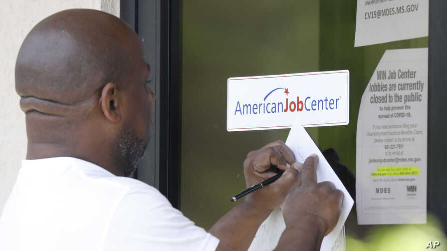 A resident copies down the Mississippi unemployment benefit website after being unable to enter the state WIN Job Center in…