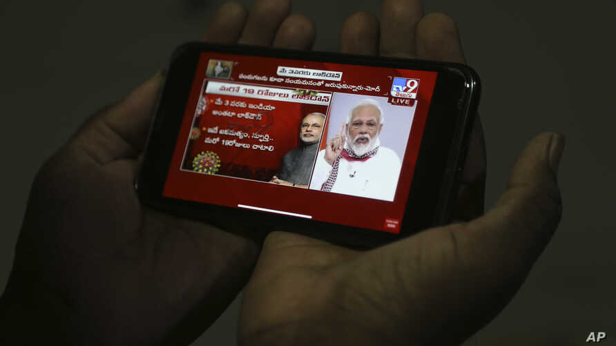 A man in Hyderabad, India watches on his mobile phone Prime Minister Narendra Modi address the nation in a televised speech…