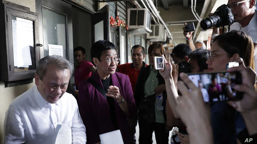 Rappler CEO and Executive Editor Maria Ressa, second from left, talks to reporters after attending a hearing at Manila Regional…