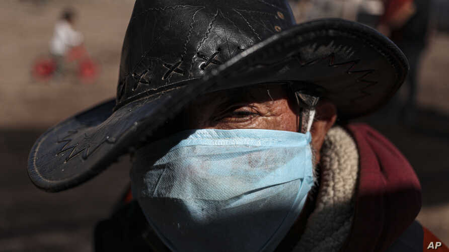 Hernaldo Gutierrez, wearing a protective face mask, waits in line to receive free fruits and vegetables from produce vendors…