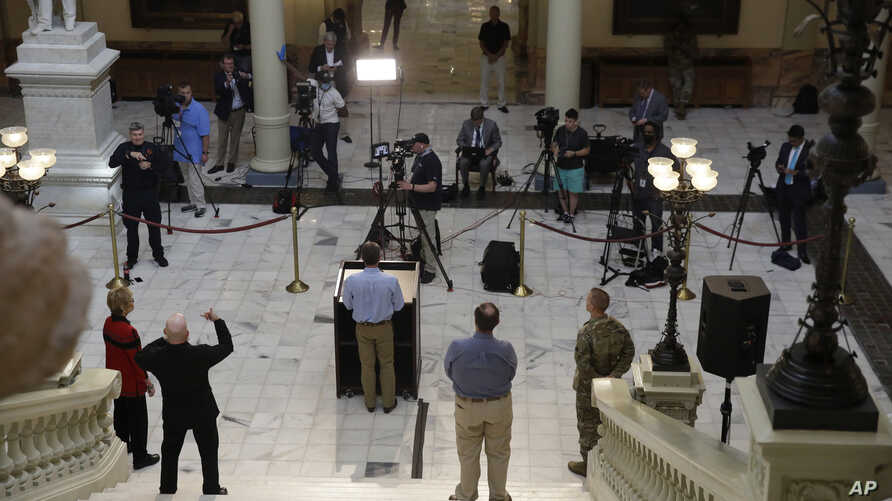 The media separates as Georgia Gov. Brian Kemp speaks about the COVID-19 virus during a news conference at the Georgia state…