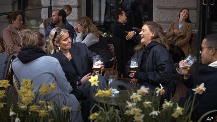 FILE - In this Wednesday, April 8, 2020 file photo people chat and drink outside a bar in Stockholm, Sweden. Sweden is pursuing…