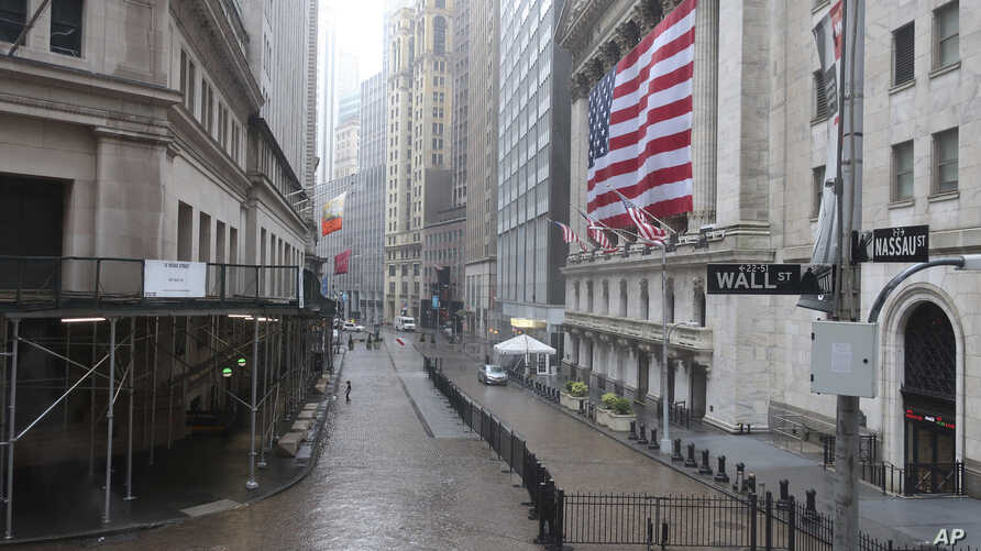 The normally busy area of Wall Street at the New York Stock Exchange is empty on a rainy day in New York, Monday, April 13,…