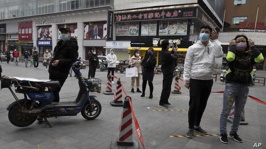 Residents wearing masks to protect against the spread of the coronavirus line up to enter a supermarket in Wuhan in central…