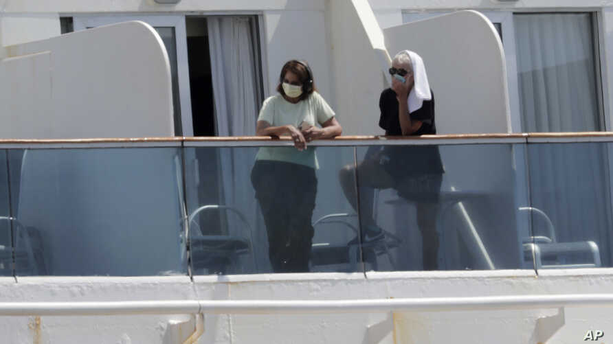 Passengers wearing protective masks look out from their balcony on the Coral Princess cruise ship while docked at PortMiami…