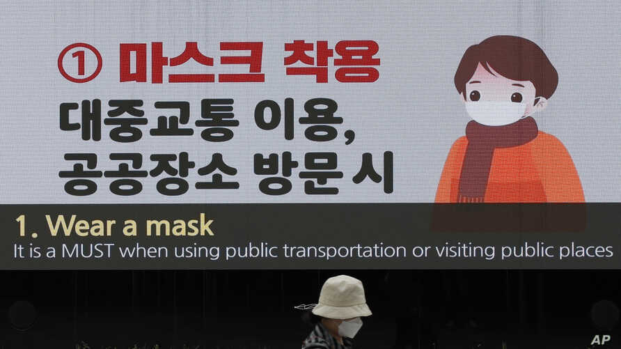 A woman wearing a face mask passes by a screen showing precautions against the coronavirus at the Dongdaemun Design Plaza in…