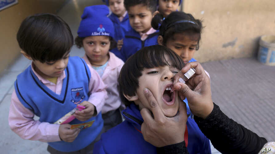 A health worker gives a polio vaccine to a child at a school in Lahore, Pakistan, Monday, Feb. 17, 2020. Pakistan government…