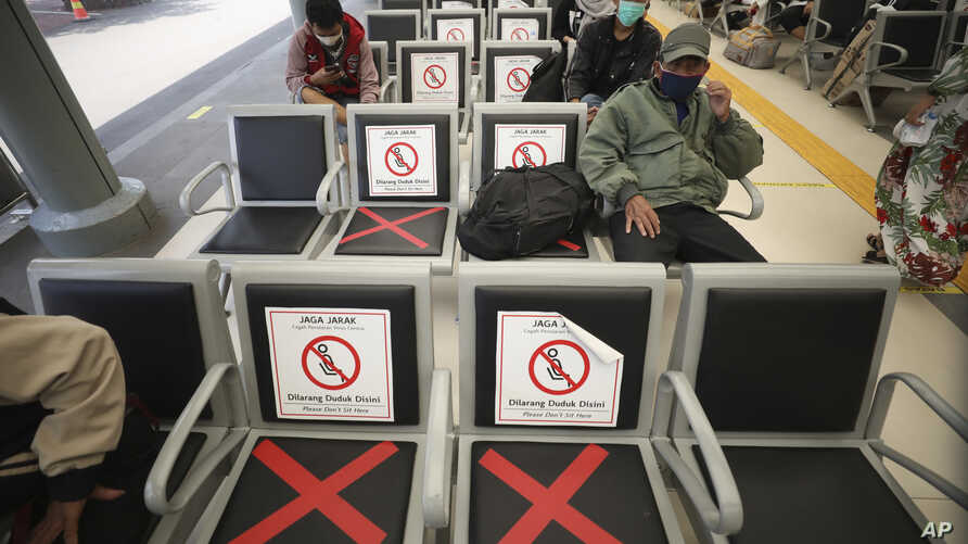 Men sit spaced apart as a social distancing effort to help curb the spread of the coronavirus in  a train station waiting area,…