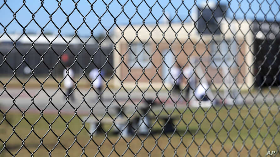 FILE - In this Sept. 26, 2019 file photo, detainees sit in a yard during a media tour inside the Winn Correctional Center in…