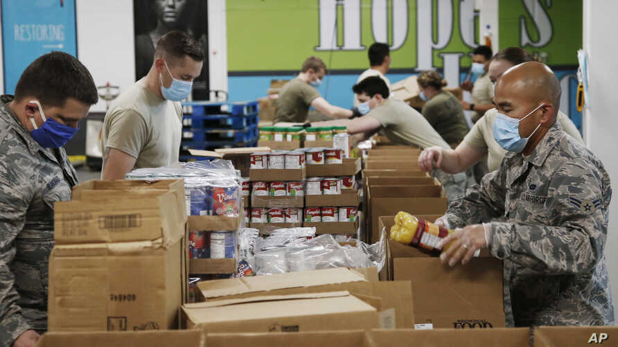 Airman First Class Binh Pham, right, and other members of the Oklahoma Air National Guard fill emergency food boxes at the…