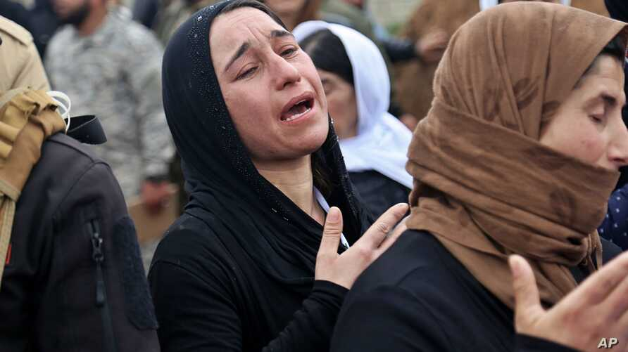 In this Friday, March 15, 2019 picture, Iraqi Yazidi women mourn during exhumation process of a mass grave in Iraq's…