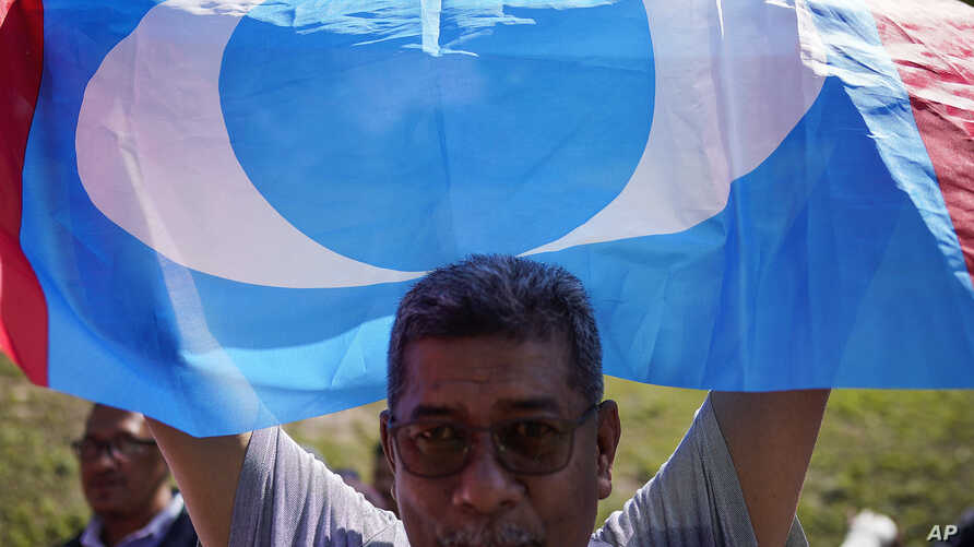 A supporter of People's Justice Party waves its party flag outside the National Palace in Kuala Lumpur, Malaysia, Wednesday,…