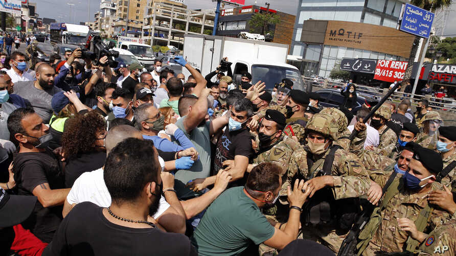 Anti-government protesters scuffle with Lebanese army soldiers in the town of Zouk Mosbeh, north of Beirut, Lebanon, Monday,…
