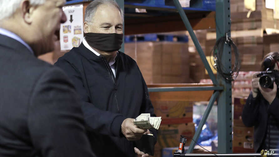 Washington Gov. Jay Inslee empties his wallet of cash to hand over to an official of Nourish Pierce County after Lakewood Mayor…