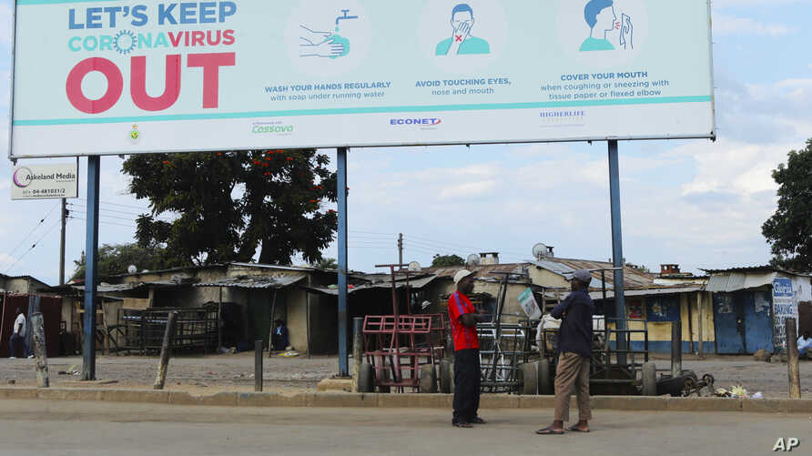 Two men stand underneath a giant poster showing advice on how to prevent the spread of the coronavirus, in Harare, Zimbabwe,…