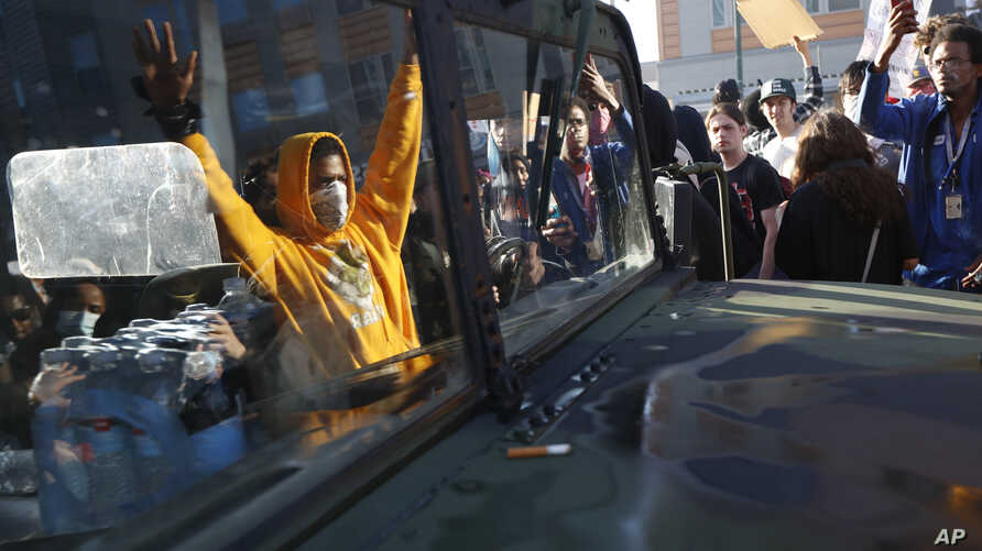 Protesters stand near a Minnesota National Guard vehicle Friday, May 29, 2020, in Minneapolis. Protests continued following the…