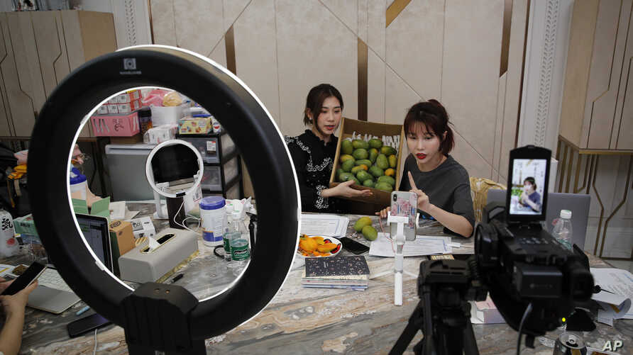 In this May 5, 2020, photo, China's online celebrity Zhang Mofan, right, introduces fresh mangos to her online clients and fans…