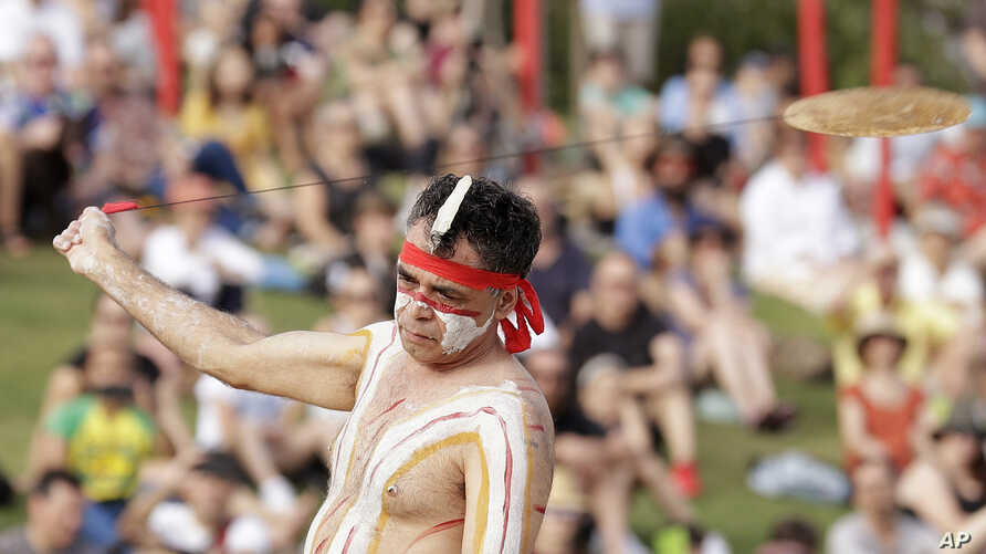 An Aboriginal man swings an instrument known as a Bullroarer during the Wugulora Indigenous Morning Ceremony as part of…