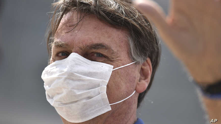 Brazil's President Jair Bolsonaro, wearing a mask against the spread of the new coronavirus, greets supporters during a protest…